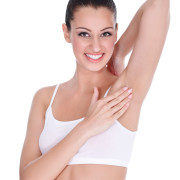 Smiling woman touching her clean armpit- isolated on white
